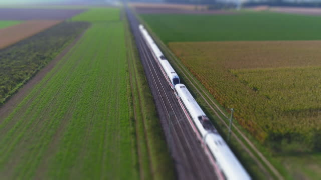 passenger train passing through countryside in autumn - schienenverkehr stock-videos und b-roll-filmmaterial