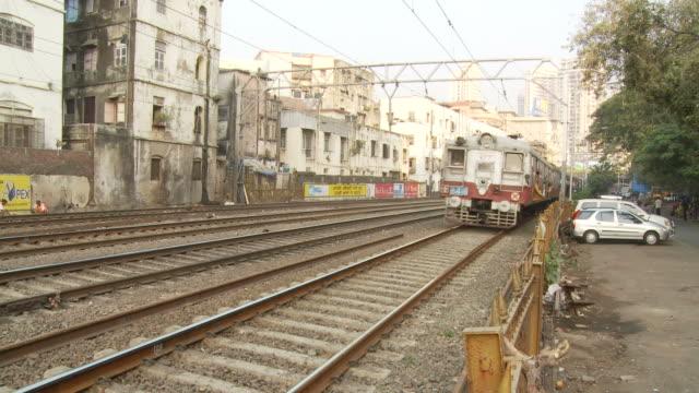 ws passenger train speeding through city / mumbai, india - mumbai stock videos & royalty-free footage