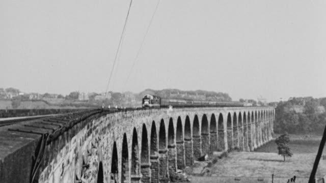 pan a passenger train traveling over a bridge / united kingdom - british rail stock videos & royalty-free footage