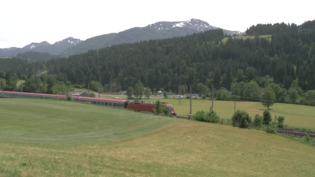 passenger train travelling through mountains near st. johann, austrian alps, tyrol, austria, europe - tyrol state austria stock videos and b-roll footage