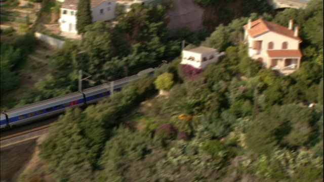 A TGV passenger train travels over a bridge and through a residential neighborhood in South of France.