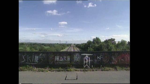 has passenger train travels towards horizon and graffiti wall; 1994 - horizon over land stock videos & royalty-free footage
