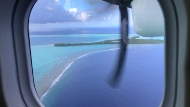 pov passenger view out an airplane window of tropical islands in french polynesia. - island stock videos & royalty-free footage