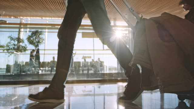 slo mo ds passenger walking across the airport terminal with a wheeled travel bag and sun shining behind him - bagaglio video stock e b–roll