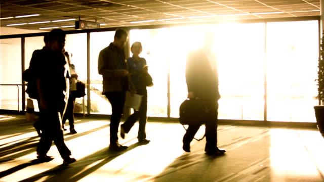 Passagerare som går i flygplatsterminalen.
