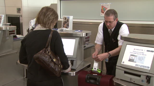 vidéos et rushes de passenger weighing luggage at kiosk at ronald reagan washington national airport / arlington virginia united states - aéroport ronald reagan