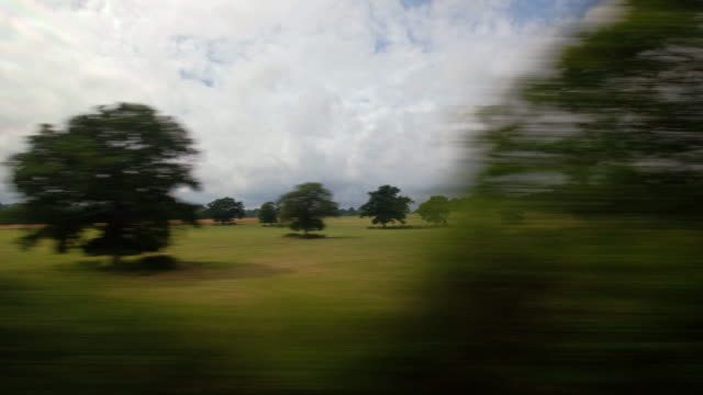 a passenger window view from a moving train traveling through the english rural countryside - zugperspektive stock-videos und b-roll-filmmaterial