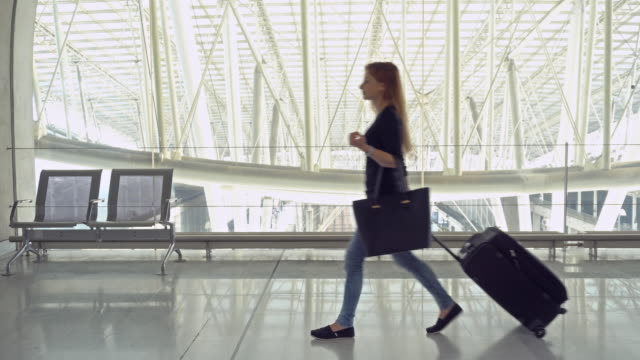 passenger with luggage walking through corridor - airport terminal stock videos & royalty-free footage