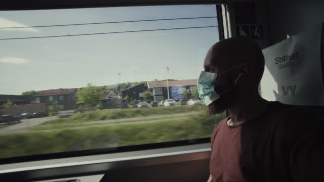 fahrgast mit maske auf der zugseite: nach sperrung in die welt reisen - schienenverkehr stock-videos und b-roll-filmmaterial