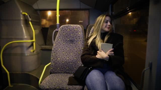 passagierfrau hält buch während der fahrt mit dem bus in der nacht. mädchen, das abends auf einem fahrenden fahrzeug neben dem fenster unterwegs war - nur junge frauen stock-videos und b-roll-filmmaterial