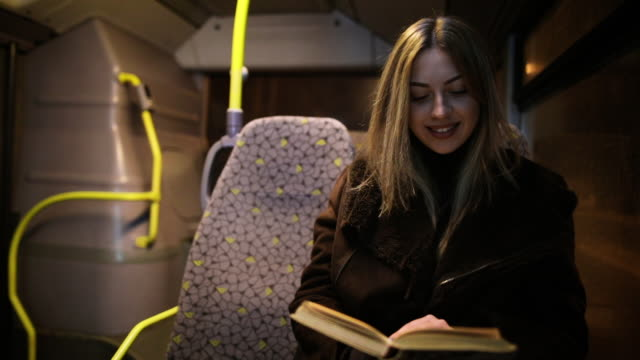 passenger woman reading book while traveling by bus at night. girl reads story in the evening on a moving vehicle next to window - reading stock videos & royalty-free footage
