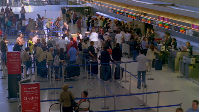 WS T/L PAN Passengers at busy airport check-in area / Los Angeles, California, USA