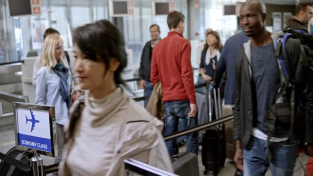 passengers at the airport walking toward the check in desk - airport terminal stock videos & royalty-free footage