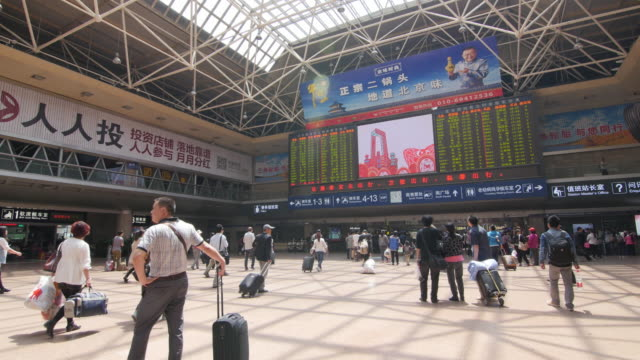 Passengers at the Beijing train station with arrival and departure board in the background.