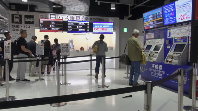 passengers at train and bus ticket windows buying tickets and information boards for departures at narita airport japan - flugpassagier stock-videos und b-roll-filmmaterial