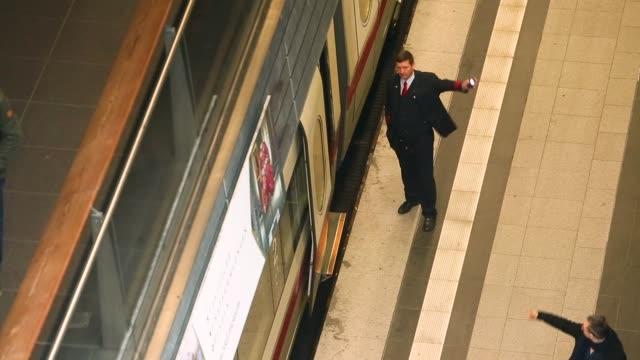 passengers await transportation as a train, operated by deutsche bahn, arrives at berlin central station, also known as hauptbahnhof. - bahnreisender stock-videos und b-roll-filmmaterial
