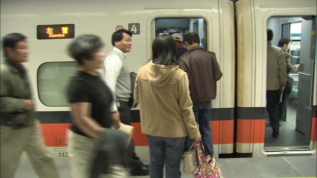 Passengers board a Taiwanese 700T model highspeed train at Banqiao Station