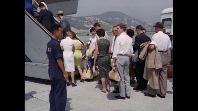 stockvideo's en b-roll-footage met montage passengers board airplane at kaitak airport in hong kong - 1963