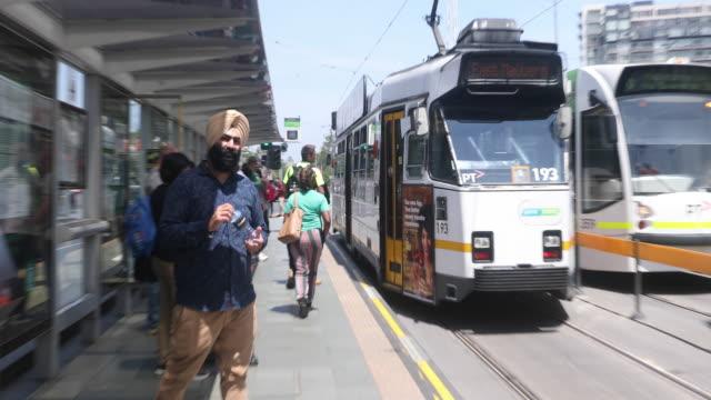 vídeos y material grabado en eventos de stock de passengers board and disembark a tram on st kilda road on december 1 2016 in melbourne australia - vía de tranvía