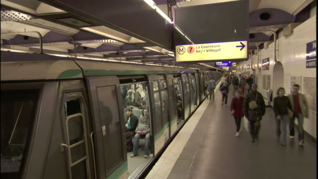Passengers board and exit a subway in Paris.