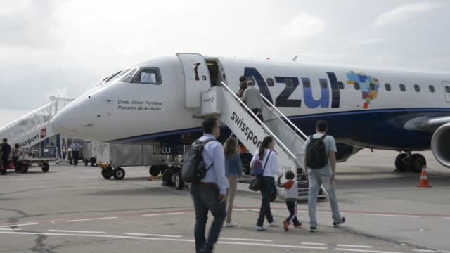 passengers board at an embraer from azul airlines airplane at viracopos international airport , campinas, brazil on wednesday, september 09th, 2015.... - azul stock videos & royalty-free footage