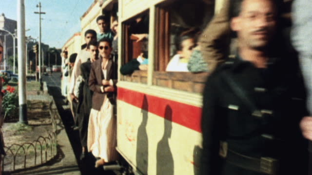 1981 montage passengers boarding a streetcar and a large passenger train cruising across a bridge / united kingdom - passeggero video stock e b–roll