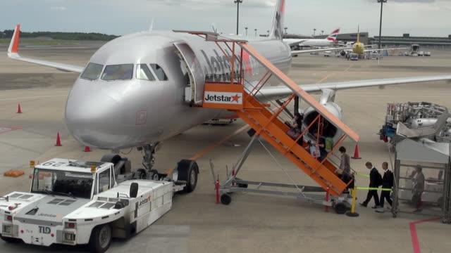 passengers boarding aircraft outdoor at narita airport tokyo japan - getting on stock videos & royalty-free footage
