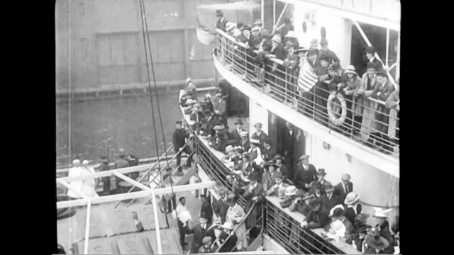 Passengers boarding ship and crowded onto balconies Author Elbert Hubert pose at the ship's rail