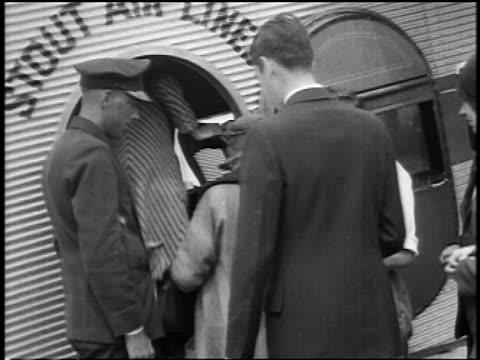 stockvideo's en b-roll-footage met b/w 1927 rear view passengers boarding stout air lines airliner / newsreel - 1927