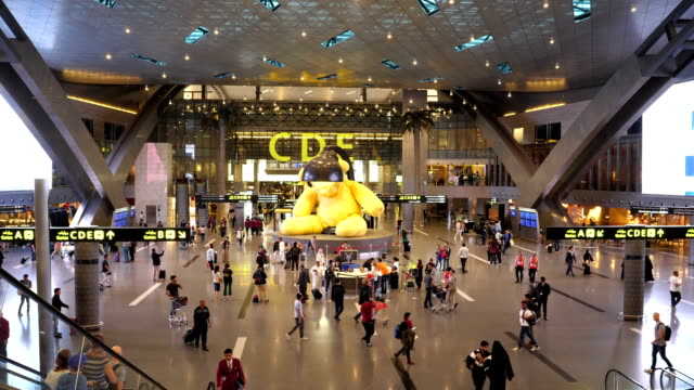 passengers business travelers and tourists in the departure hall of the airport of doha qatar 4k resolution - ad dawhah stock-videos und b-roll-filmmaterial