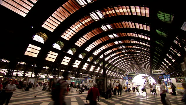 Passengers bustle along the platforms of the Milano Centrale railway station. Available in HD.