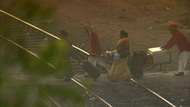 passengers carry luggage as porters push a loaded cart over train tracks. available in hd - push cart stock videos & royalty-free footage