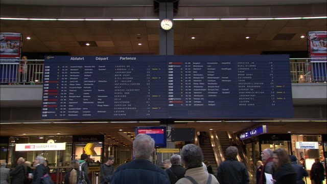 passengers check arrival and departure boards in a train station in bern. - bahnhof stock-videos und b-roll-filmmaterial