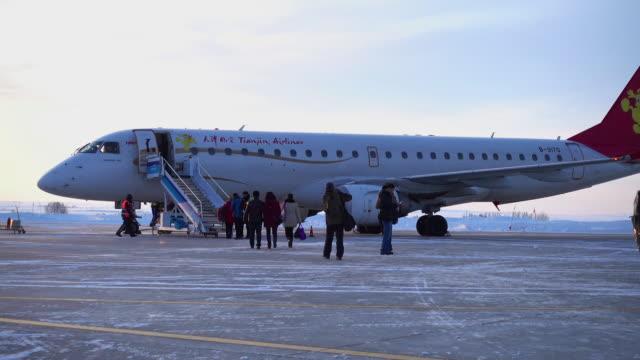 Passengers climbing stairs to board airplane.
