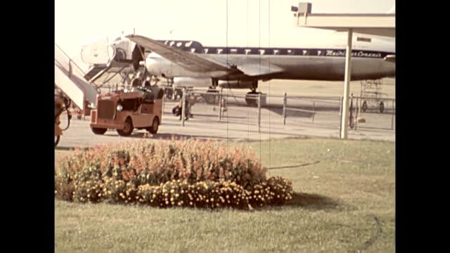 passengers disembark from a united convair cv580 mainliner propeller driven aircraft / closeup pan of aircraft   female aircrew disembarks and ducks... - flugpassagier stock-videos und b-roll-filmmaterial