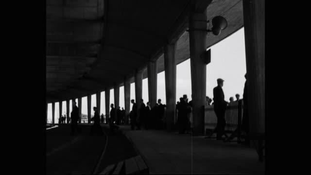 vidéos et rushes de passengers disembarking ocean liner and walking towards train at railroad station - navire