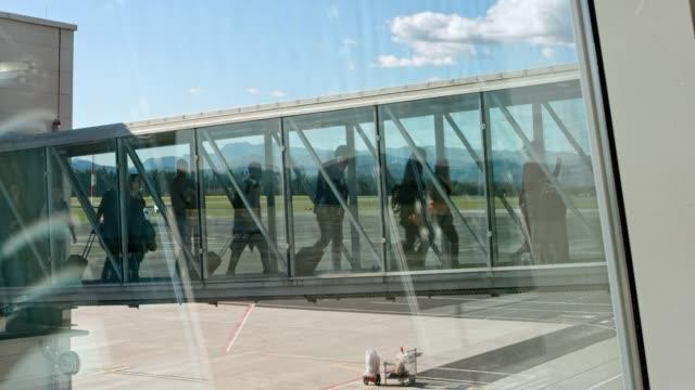 ld passagiere das flugzeug über eine glasbrücke jet aussteigen - getting out stock-videos und b-roll-filmmaterial