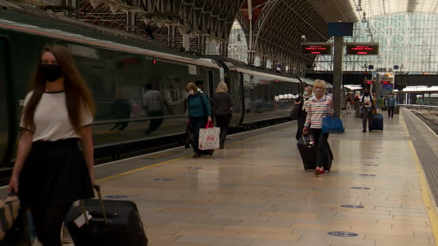 passengers disembarking train at paddington train station wearing face masks as it becomes compulsory in england to wear a face covering on public... - railway station stock videos & royalty-free footage