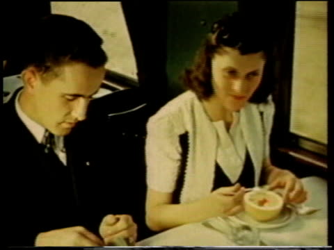 1941 MONTAGE Passengers eating in the dining car aboard a passenger train / United States