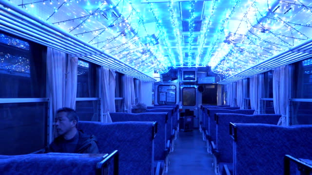 "passengers enjoy the dazzling illuminations of blue ""winter fireflies"" created with led lights on their journey in a singlecar train running on asa... - tokushima prefecture stock videos & royalty-free footage"
