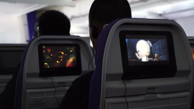 passengers enjoying movies and games on an airbus plane during flight. - passagier stock-videos und b-roll-filmmaterial