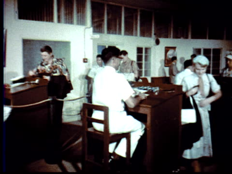 1957 MONTAGE Passengers enter Singapore airport gate + present passports to customs inspectors / Singapore / AUDIO