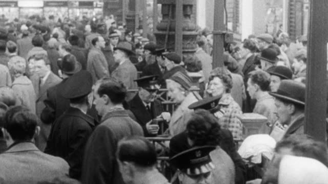 vídeos de stock, filmes e b-roll de 1965 montage passengers entering turnstiles and crowding loading platforms at train station, with cars parked on street outside and with dr. beeching narrating / united kingdom - narrating