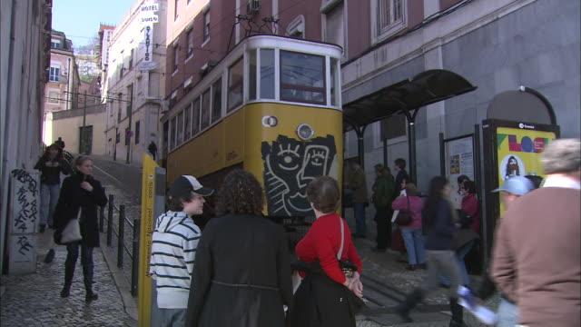 vídeos de stock e filmes b-roll de passengers exit a train as pedestrians pass by in lisbon, portugal. - linha do elétrico