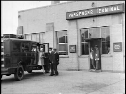 b/w 1927 passengers exiting van + entering terminal of early airline / newsreel - flugpassagier stock-videos und b-roll-filmmaterial