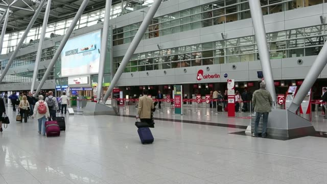 passengers go up and down escalators in the departures terminal at dusseldorf airport operated by flughafen dusseldorf gmbh in dusseldorf germany on... - デュッセルドルフ点の映像素材/bロール
