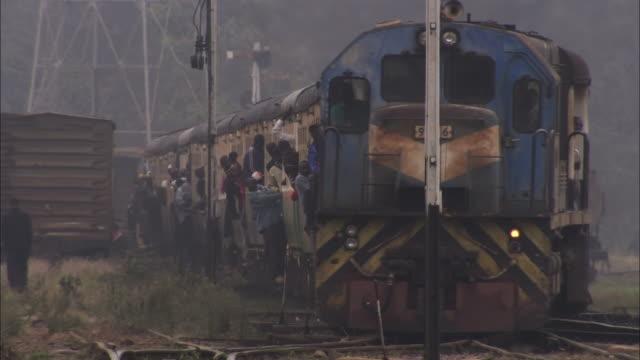 ws passengers hanging out of doors in crowded train arriveing / nairobi, nairobi province, kenya - nairobi stock videos and b-roll footage