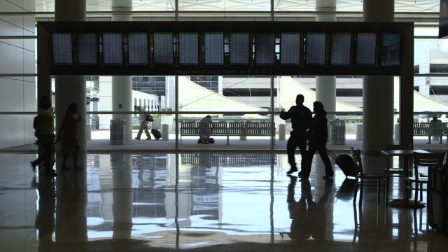 Passengers  (silhouette) in airport terminal walk around departure-arrival display/DFW International Airport, Dallas-Fort Worth, Texas, USA