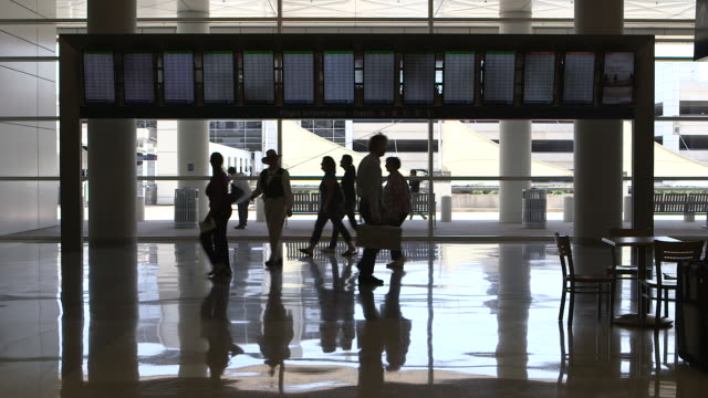 passengers  (silhouette) in airport terminal walk around departure-arrival display/dfw international airport, dallas-fort worth, texas, usa - dallas fort worth airport stock videos & royalty-free footage