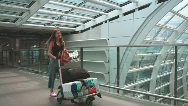 passagiere der fluggesellschaft gingen, um das gepäck zum gate zu schleppen. in der passagierhalle - flugpassagier stock-videos und b-roll-filmmaterial